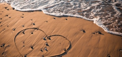 heart drawn in the sand with a wave coming in