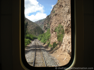 Train tracks going through brown canyons framed by a window